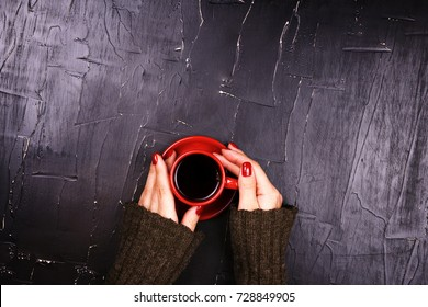 Girl holding red Cup of coffee on dark background