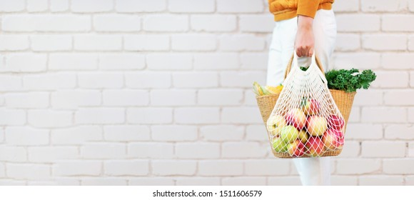 Girl holding reusable mesh bag full of apples, straw basket with organic vegetables. Banner. Copy space. Autumn harvest. Sustainable eco lifestyle. Zero waste, plastic free concept