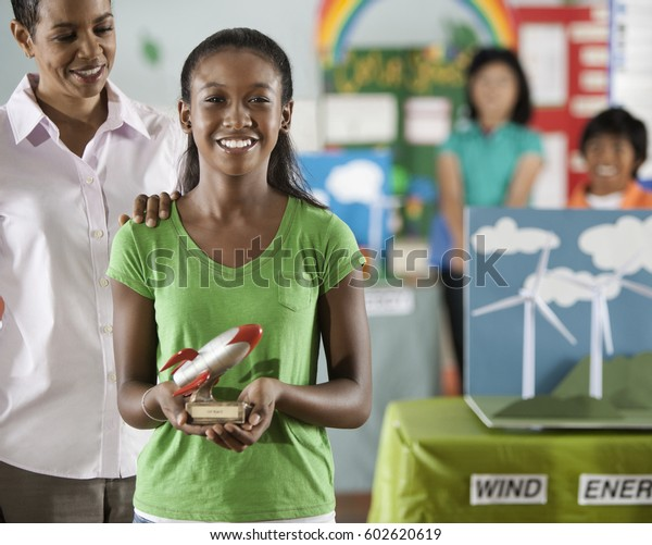 A girl holding a rocket trophy in front of a group of students at the Green Science Fair,