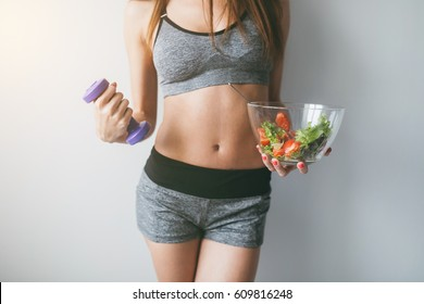Girl holding salad and dumbbell after fitness training.