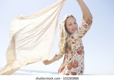 Girl holding a sarong in the air blowing in the sea breeze.