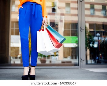 Girl holding shopping bags in one hand, legs in blue trousers