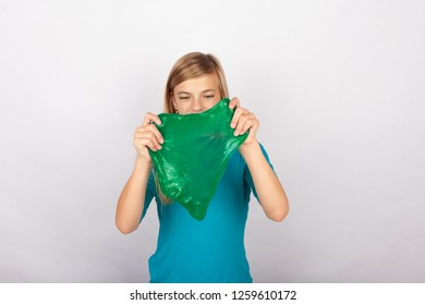 Girl holding a slime in front of her face.