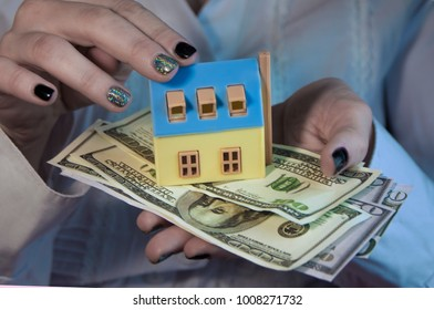 the girl holding a small house and money