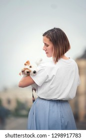 girl holding small parson russell terrier dog in her arms and looking at her. Dog looking at camera.