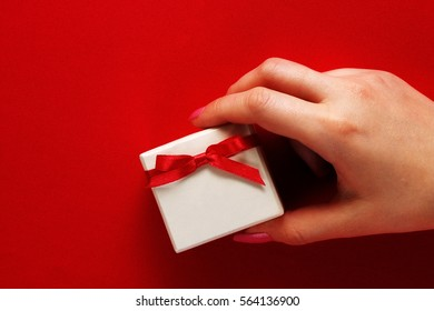 Girl holding a small white gift box with a red bow on a red background.