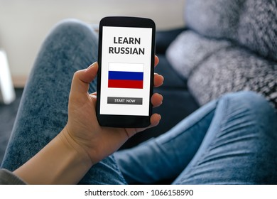 Girl holding smart phone with learn Russian concept on screen. All screen content is designed by me