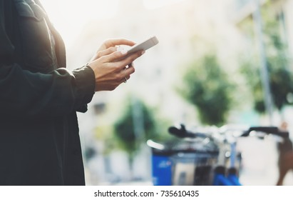 Girl holding smart phone on background sun atmospheric city and bike, hipster using in female hands and texting mobile, street lifestyle and flare sun, tourist planing route in summer, gadget concept