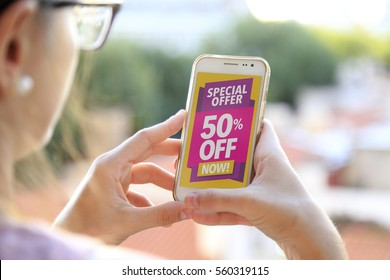 Girl holding a smartphone with a 50% discount advertising on the screen. Marketing, ecommerce, cell phone publicity.