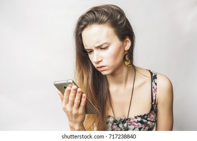 A girl is holding a smartphone in her hand and is looking for something there, made a mistake, does not understand. Angry