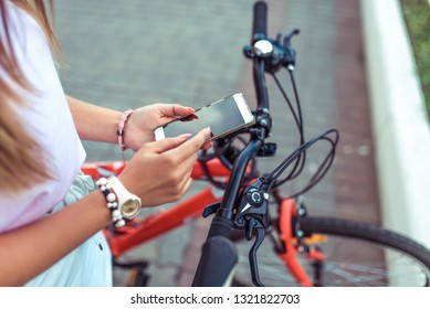 Girl is holding smartphone, searching route application in Internet map. Against the background of red black bicycle in parking lot. Online in social networks, communication correspondence.