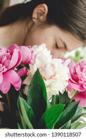 Girl holding and smelling beautiful pink and white peonies bouquet at rustic old wooden window. Floral decor and arrangement. Gathering flowers. Rural still life, countryside