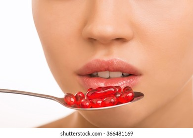 Girl holding a spoon with pills at her mouth.