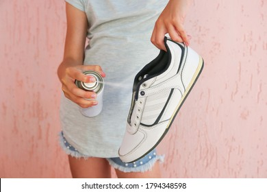 Girl holding spray deodorant for shoes.