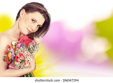 Girl holding spring flowers. Bokeh background with flowers.