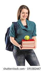 Girl holding a stack of books and an apple on top isolated on white background