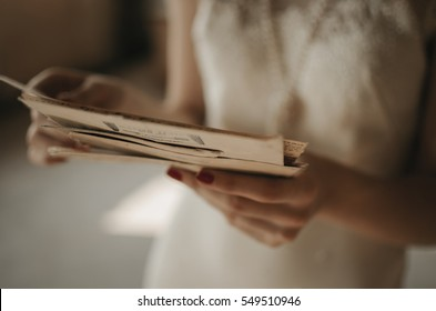 A girl holding a stack of old letters.
