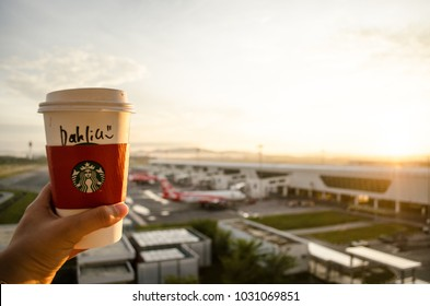 """A girl holding a Starbucks cup with her name written on it """"Dahlia"""" during sunrise  in  The domestic airport of Kuala Lumpur  in Malaysia in November 2017"""
