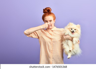 girl holding stinky stray dog, dirty pet needs to be washed, bad smell from dog's mouth. unpleasant smell from pet