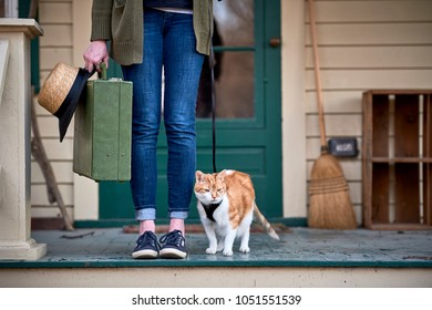 a girl holding a suitcase and going on a trip with her cat