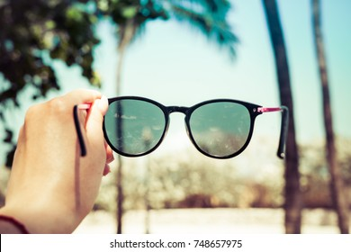 The girl is holding sunglasses in her hand against the background of blurry palms. Travel concept