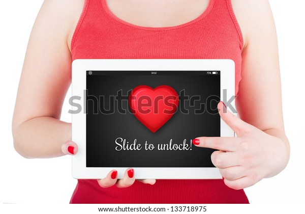 """A girl is holding a tablet computer, which shows the heart and inscription """"Slide to unlock"""". Isolated on white."""