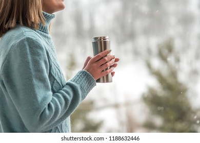 A girl holding a thermos with a hot drink. A mug of coffee in her hands. Winter