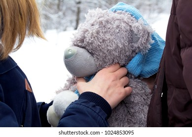 A girl is holding a toy in her hands, a teddy bear, a gray bear.  Winter, snowy day