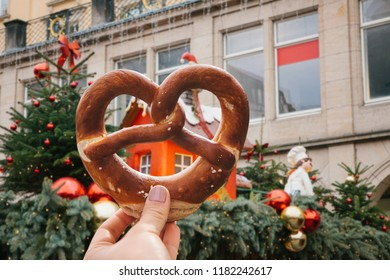 The girl is holding a traditional German pretzel in her hand. Decorations of a Christmas market in the background.