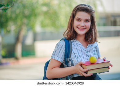 girl holding two books red and green and smiling. Schoolgirl on background of school after summer holidays. Ready to start school year schoolgirl. Back to school.