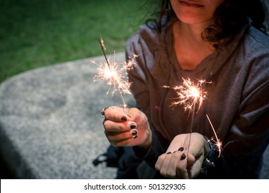 Girl is holding two sparking firework or firecracker alone