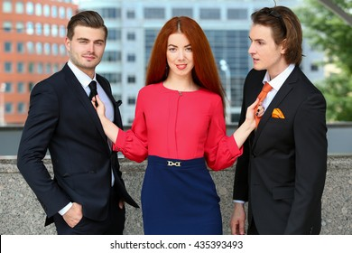girl holding two young men tie