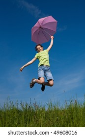 Girl holding umbrella, jumping against blue sky
