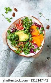 Girl holding vegan, detox Buddha bowl with turmeric roasted  chickpeas, greens, avocado, persimmon, blood orange, nuts and pomegranate.