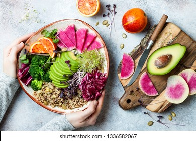 Girl holding vegan, detox Buddha bowl with quinoa, micro greens, avocado, blood orange, broccoli, watermelon radish, alfalfa seed sprouts.