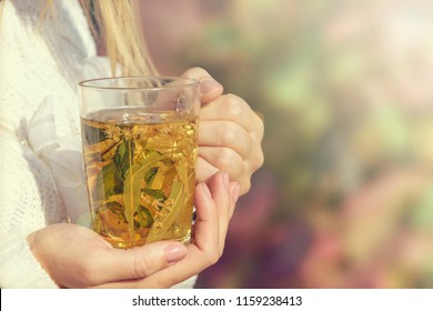 The girl is holding a warm warming herbal tea close-up.Copy space.Toned