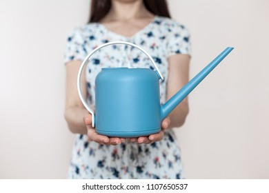 Girl holding a watering-can in her hands on a light background