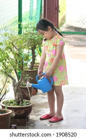 Girl holding watering-can watering the plant