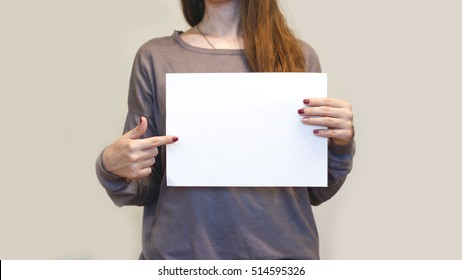 Girl holding white A4 blank paper horizontally. Leaflet presentation. Pamphlet hold hands. Woman show clear offset paper. Booklet design sheet display read first person. Pointing finger.