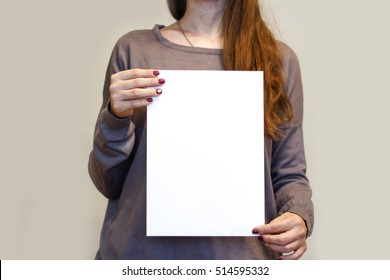 Girl holding white A4 blank paper vertically. Leaflet presentation. Pamphlet hold hands. Woman show clear offset paper. Booklet design sheet display read first person.