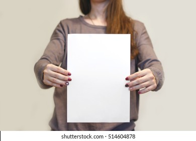 Girl holding white A4 blank paper vertically. Leaflet presentation. Pamphlet hold hands. Woman show clear offset paper. Sheet template. Booklet design sheet display read first person.