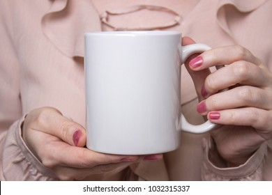 Girl is holding white cup in hands. White mug for woman, gift. Mockup for designs