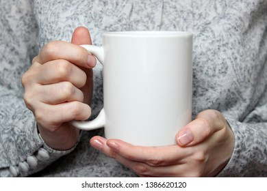 Girl is holding white cup in hands. White mug for woman, gift. Mockup for designs.