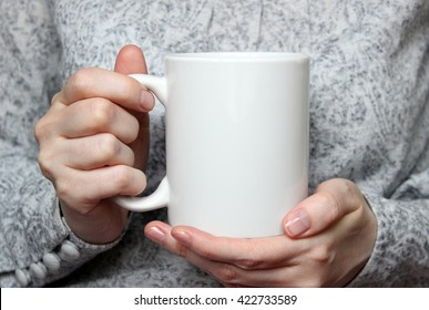 Girl is holding white cup in hands. Mug for woman, gift. Mockup for designs.