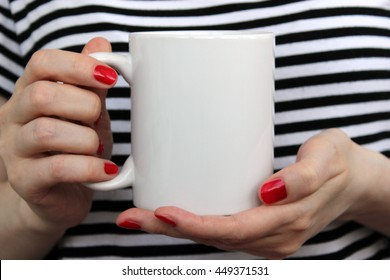 Girl is holding white cup, mug in hands. Mockup for designs.