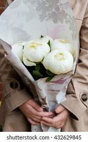 Girl is holding white peonies bouquet wrapped in a paper, spring or summer concept, selective focus
