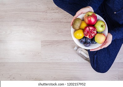 Girl holding white plate with apples, plums, kiwi and pomegranate. Healthy eating. Fitness and healthy lifestyle concept. Top view