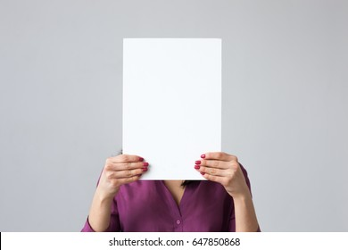 The girl is holding a white sheet of paper in her hands, covering her face.