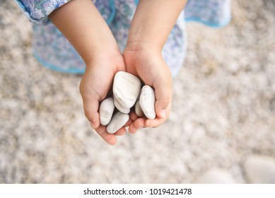 girl holding white stones in hands at beach