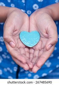 Girl holding wood shape of heart . Concept for giving love.
